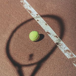 yellow tennis ball on the court